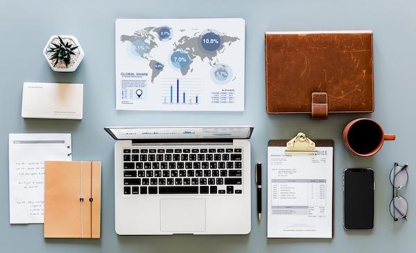 FloQast Month-end Close Guest Blog - Laptop, map, desk supplies overhead view - SuiteCentric