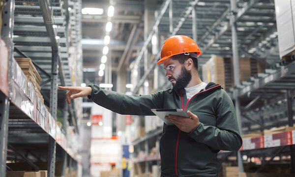 Warehouse worker in front of shelving, netsuite wholesale distribution